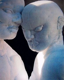 On a dark grey background, a close-up of soft sculpture heads, Kouros and Koure leaning into eachother
