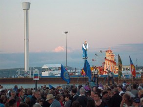 early evening view over crowds to an overhead acrobat on the beach at weymouth for the Olympic Opening ceremony