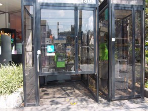 This is a photograph of two telephone booths, one twice as wide as the other. they are both black metal framed with lots of glass. The door of the wider both does not extend to the ground, but stops about 3/4 of the way down. the handle is close to the bo