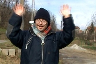 shows a man in glasses outdoors smiling at the camera and holding up his hands