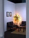 The photograph shows a doctor's waiting room installed in an art gallery. There are two identical chairs, a square coffee table and carpet. Framed photos on the white walls show pictures of other waiting rooms