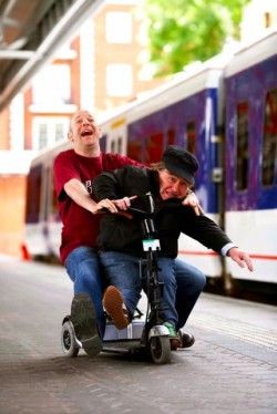 two men laugh whilst riding a mobility scooter in a railway station