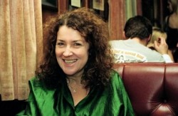 photo of a woman with dark curly hair wearing a green top