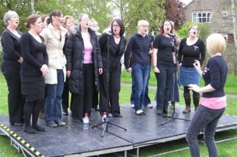 the kaos signing choir, pictured rehearsing in an outdoor space