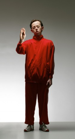 photo of a young man in a red outfit standing, facing the camera with one hand held aloft