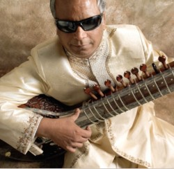 photo of musician Baluji Shrivastrav sitting, playing a sitar