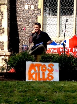 photo of performance poet Bonk sitting outside a church with a microphone in his hand. A poster which reads
