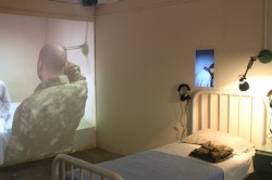 A photograph taken from Caglar Kimyoncu's installation COnscription showing a hospital bed with army fatigues folded up on it. Headphones are on the wall above the bed and a projection is screened on the opposite wall.