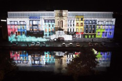 Cork's College of Commerce is lit up with a projection depicting colourful buildings with an Invacar driving down the projected street emitting blue smoke