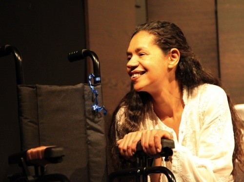 photo of actress Jaye Griffiths facing the camera side-on, with a smile on her face. She sits beside a wheelchair