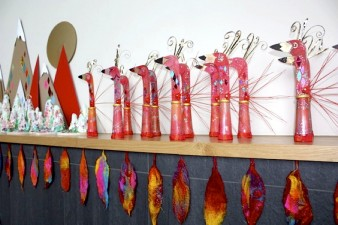 image of a series of red mouse puppets lined up along a shelf against a white wall