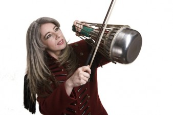 Photo of percussionist Evelyn Glennie playing a waterphone with a bow