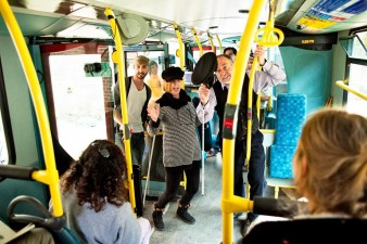 a woman and a bus driver, both carrying white canes entertain a group of people aboard a double decker bus