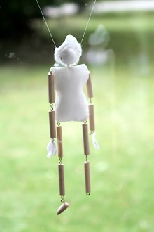 image of a cloth and wood marionette hanging against a green background