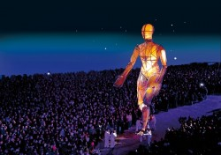 a massive figure is lit up from within with crowds watching
