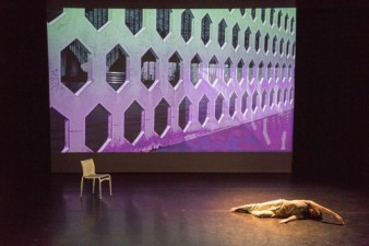 Photograph of contemporary dancer Housni Hassan aka DJ. He is lying down on a stage, a projected image behind him and a chair at the other end of the stage.