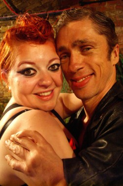 Alice Holland and Mat Fraser hug and smile at a party, both dressed in black leather