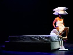 photo of a dance performance where a man sits on a bed holding a woman's foot who has pillows on her head