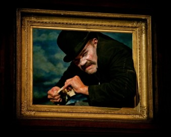 an actor wearing a bowler hat peers out of a classical picture frame