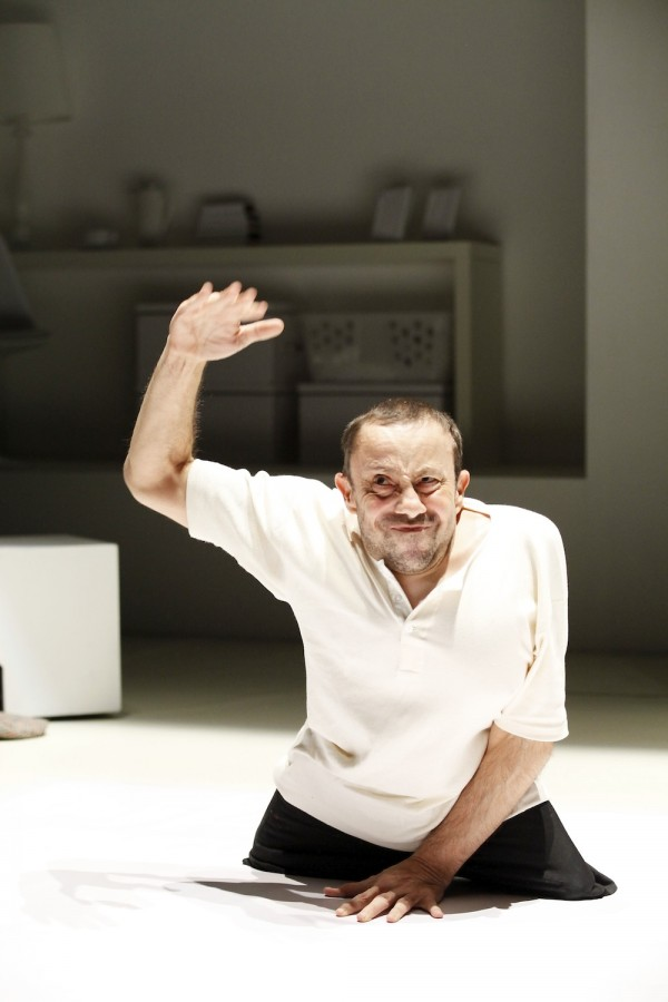 male acting - without legs - faces the camera, one hand on the floor and one hand raised in the air