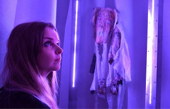 photo of the author inside an installation with brilliant purple folds and a cloth with a frightening face
