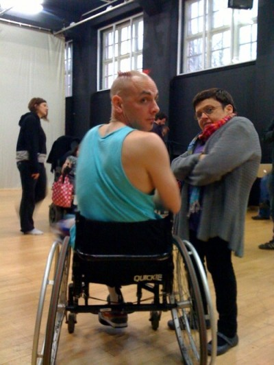 photo of the back of a wheelchair-user turning around to look at the camera. A woman of short stature tands close by