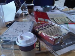 Image of table littered with books and paperwork including the book Loyal Enemy.