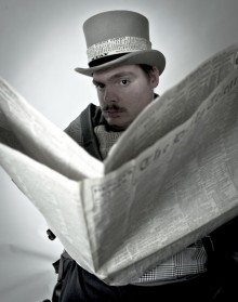 photo of an actor looking at the camera, dressed in a grey top hat and coat