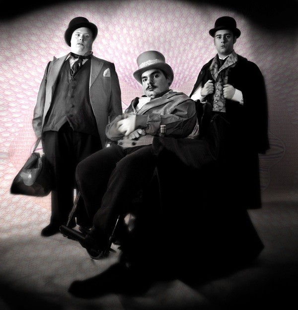 photo of three actors dressed in victorian clothes smiling at the camera