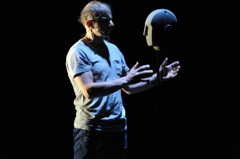 Performer Simon McBurney faces a futuristic black mannequin head, his hands either side of it.