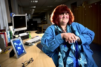 photo of disabled woman Sarah Bush at her work desk with computer and iPad