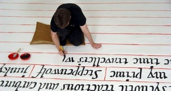 photo taken from above of a person writing in large calligraphic letters on a white floor with red lines