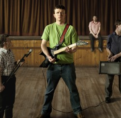 a photo of a  young man in a green t-shirt posing with an electric guitar