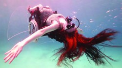 Woman scuba diving in wheelchair leaning back with long hair flowing out.