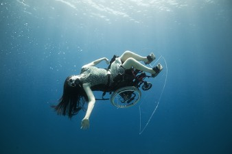 Artist Sue Austin performing in wheelchair flying mid water in deep blue sea