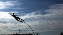 photo of a young man flying high on a swaypole against a brilliant blue sky