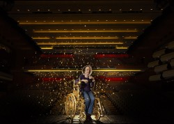 A photograph of Liz Carr on stage at the Royal Festival hall. She is using a golden wheelchair with confetti all around her.