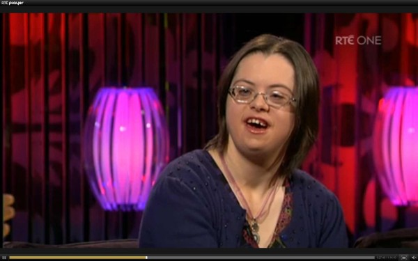photo of Aimee Richardson in the RTE television studio with pink lights on stands behind her