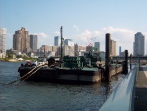 An old and battered river-barge moored to the Sumida walkway