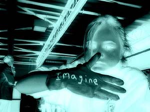An image that looks like a photo negative of a girl holding up her hand with a glove and 'imagine' written on it