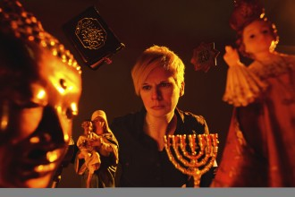 photo of performer Claire Cunningham under a red light surrounded by religious imagery