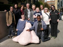 A photograph of a group of young learning disabled people outside the Birmingham Hippodrome, they have a large paper maiche nose in front of them.