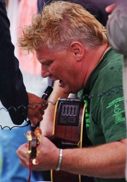 Photo of Photo of Johnny Crescendo singing and playing guitar