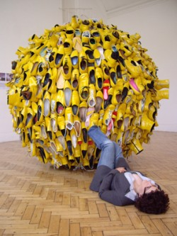 a large ball of yellow painted shoes with artist lying on the floor