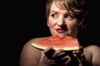 photo of performer Caroline Bowditch holding a large slice of watermelon