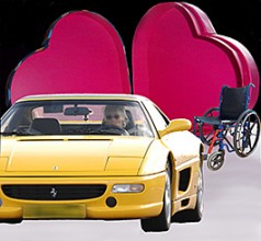 With the open heart-shaped box as background, there is infront of it an NHS wheelchair and a yellow ferrari
