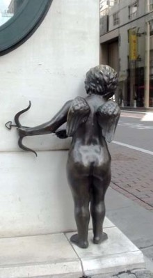 photo of a statue of cupid peering around the corner at pavement level