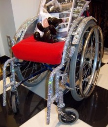 The manual wheelchair covered in crystal sparkle. It has a bright red cushion and sits on a black and white tiled floor.