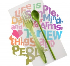 a green plastic fork and spoon, the fork is translucent, the spoon opaque; they are imposed upon the outline profile of a child's head which is made up of rainbow coloured words and a heart