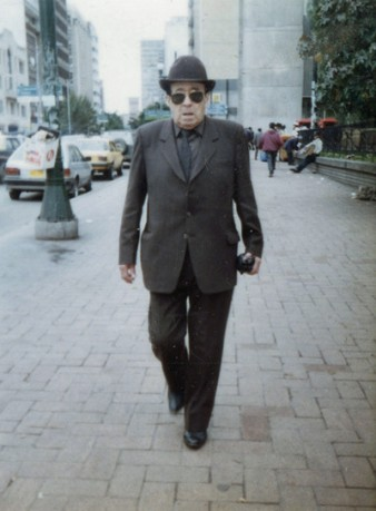 image of a man on a street wearing a suit, hat and dark glasses